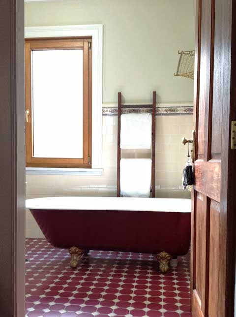 Vintage ladders are used for extra towel hanging space in both bathrooms