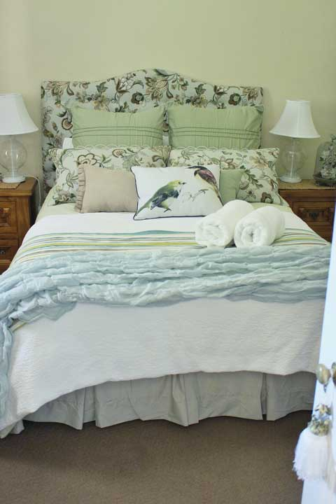 The bird guest room has vintage cupboards and dresser, plus decor items like an old type writer and french advertising prints