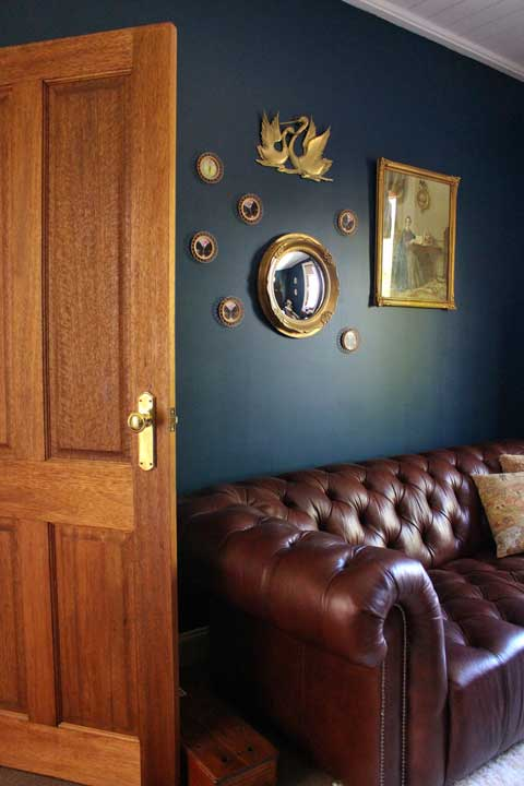 The parlour walls are adorned with vintage items - old prints, a convex mirror and old butterfly coasters. the first aid kit is contained in the old telephone box near the door in the picture.